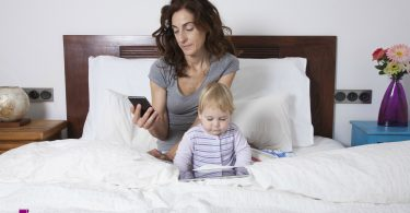 eighteen month aged blonde baby watching digital tablet and brunette woman mother at smartphone on white bed