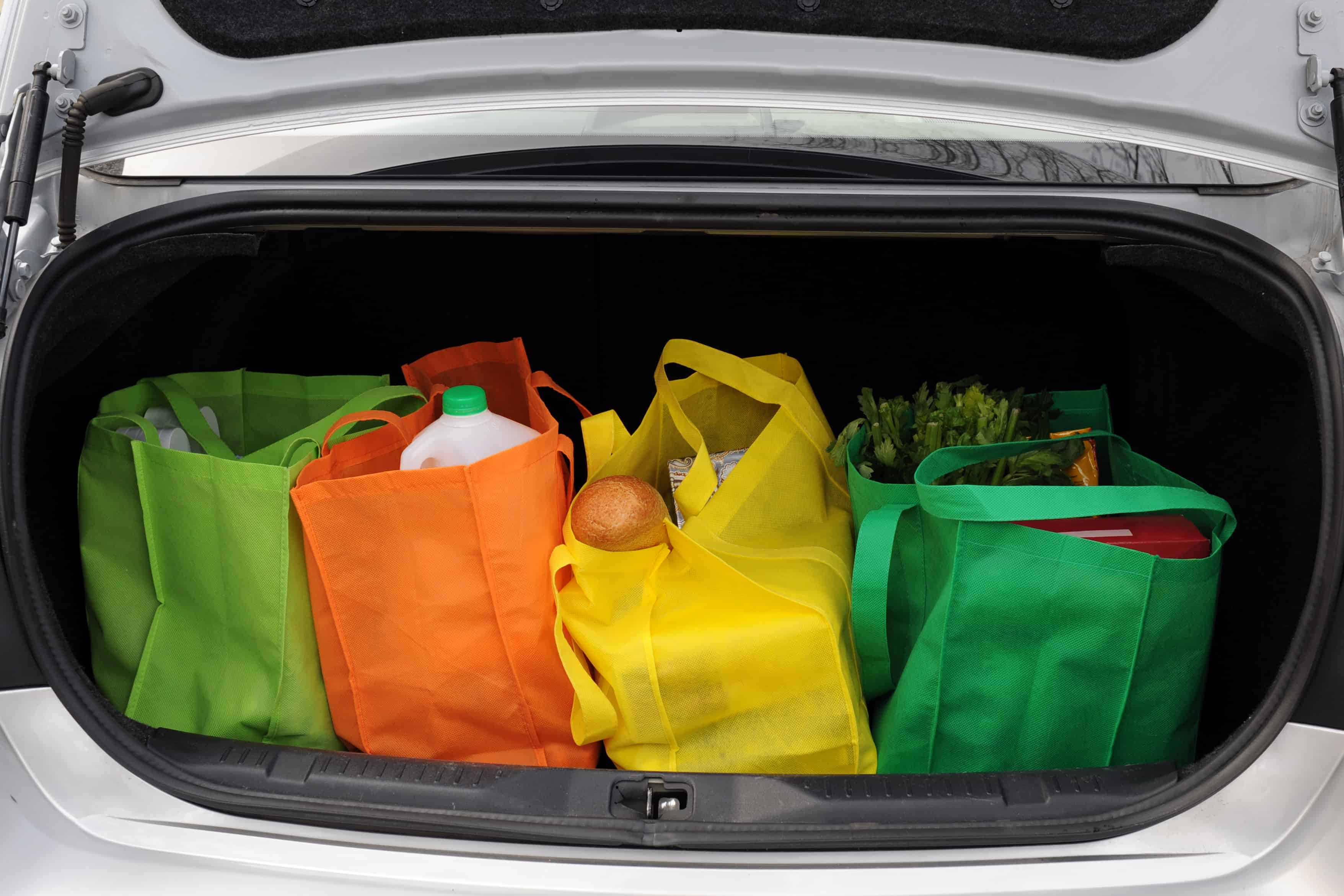 Four colorful eco-friendly shopping bags filled mostly with groceries in the trunk of a car.