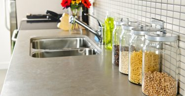 Modern small kitchen interior with glass jars on natural stone countertop