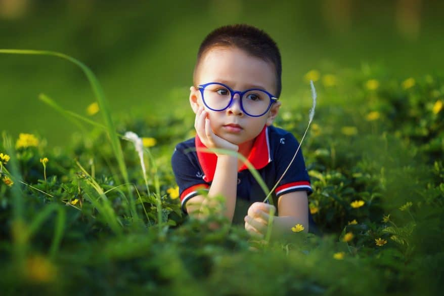 boy in the grass blue glasses