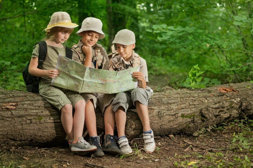 kids looking at a map while hiking