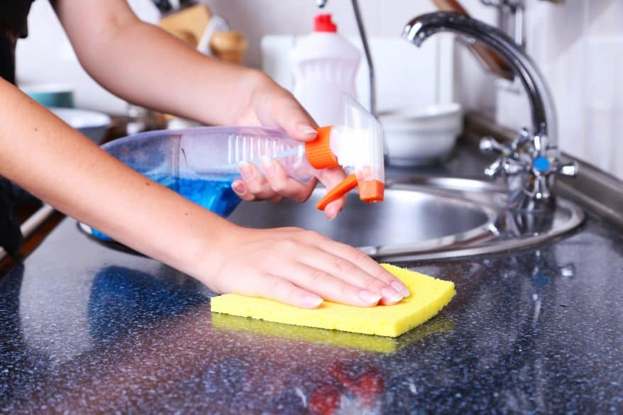 Cleaning kitchen with spray and sponge
