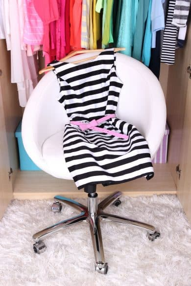Female clothes in wardrobe and chair in room