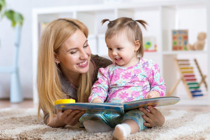 happy mother reading a book to child girl at nursery