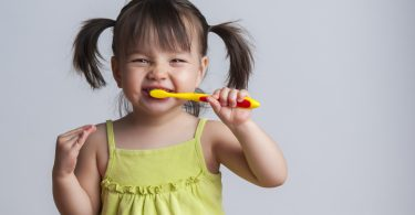 Toddler smiling while brushing her teeth kids' bathroom organization