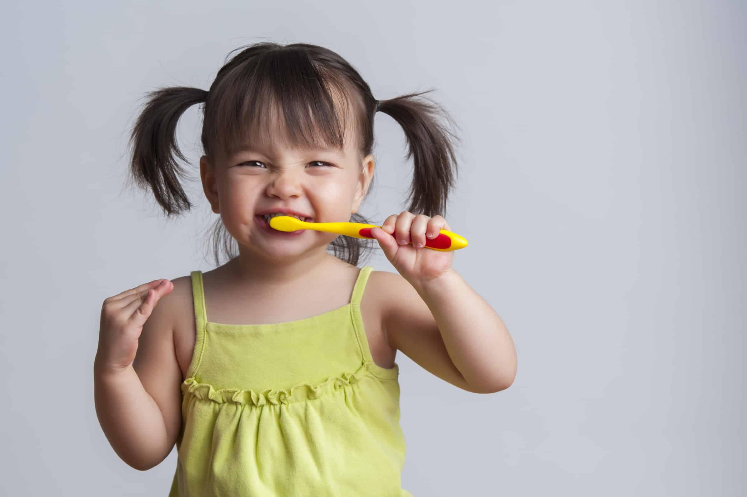 Toddler smiling while brushing her teeth kids' bathroom organization