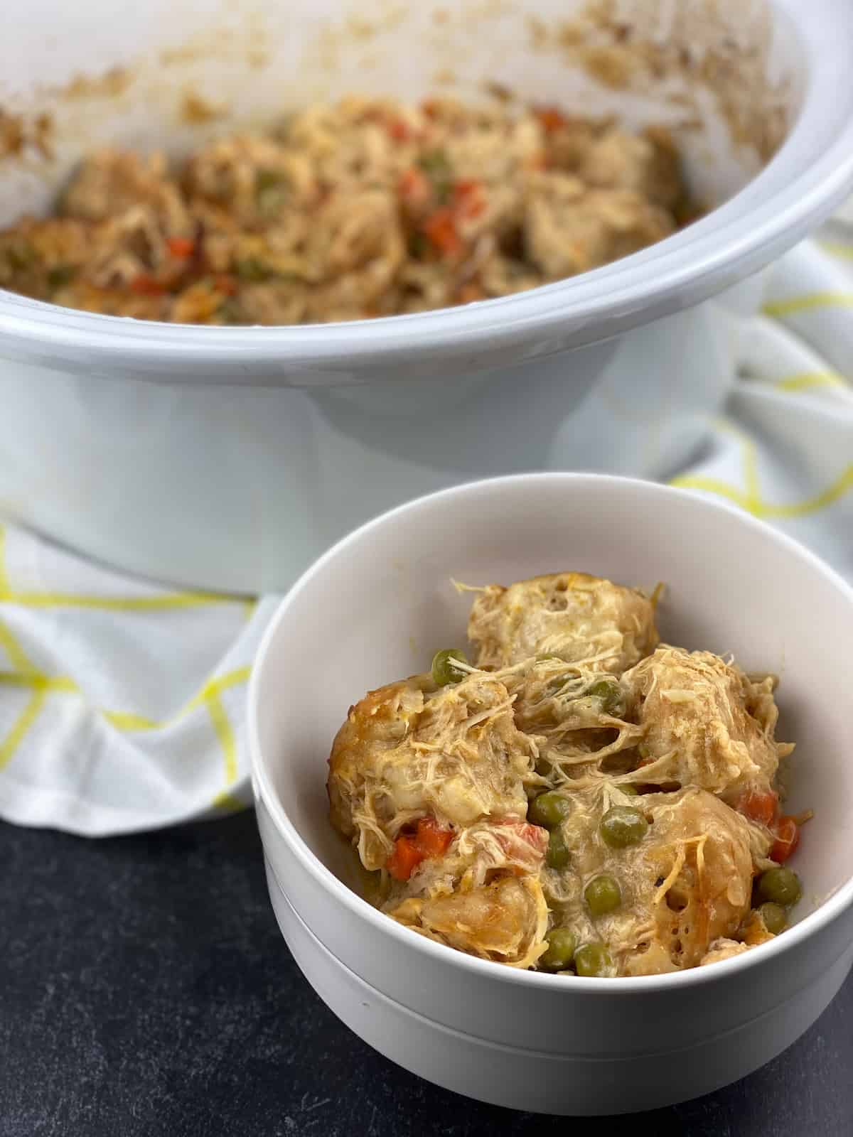 crock pot insert with bowl of chicken and dumplings made with canned biscuits