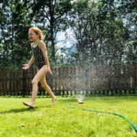 Girl in sprinkler