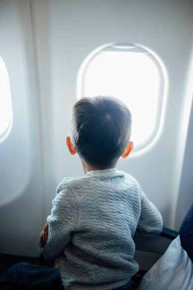 child in airplane flying with young children